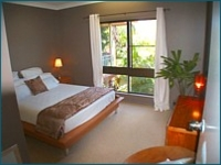 Rainforest Mission Beach Apartments - main bedroom, queen bed, white linen and palm trees through the windows.
